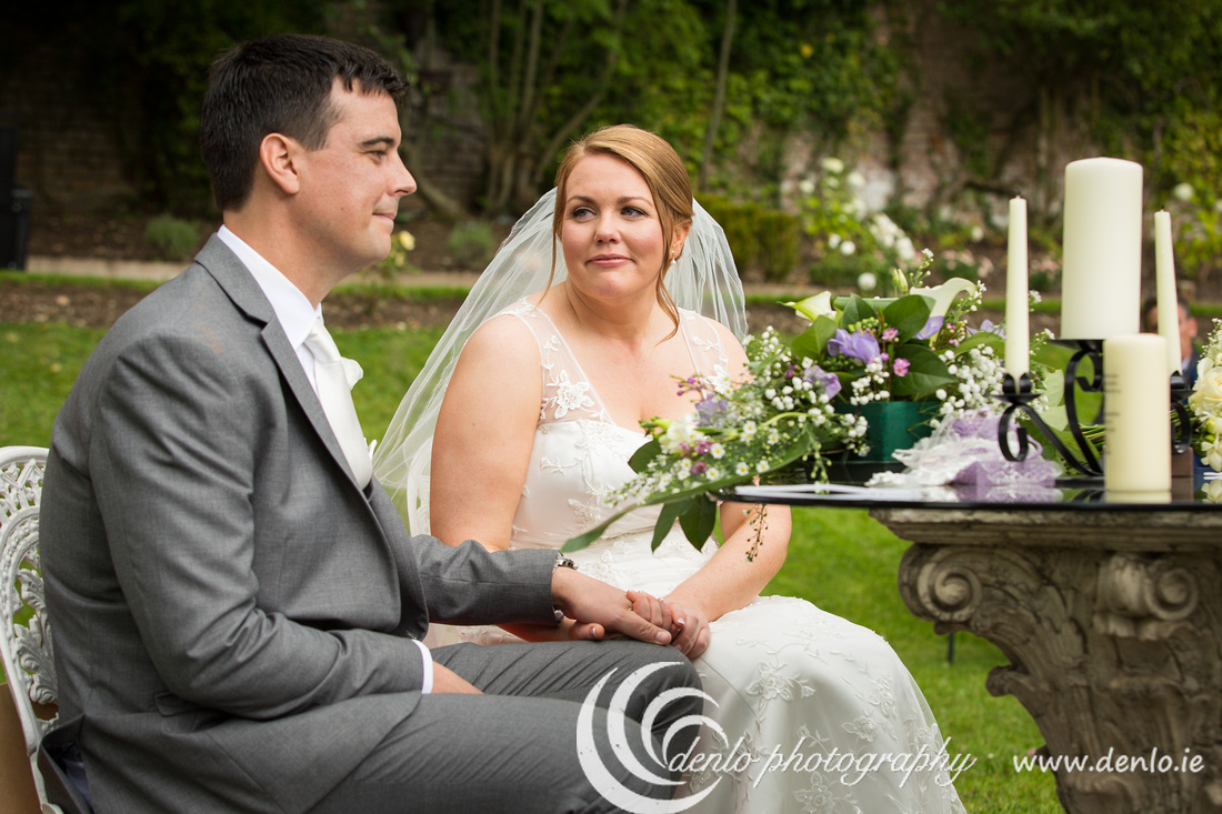 Bride and groom holding hands during their wedding ceremony at Boyne Hill House
